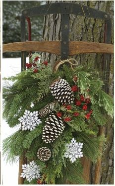Christmas wreath hanging on old fashion snow sled. Painted pine cones. Holly berries. Ornamental snow flakes.