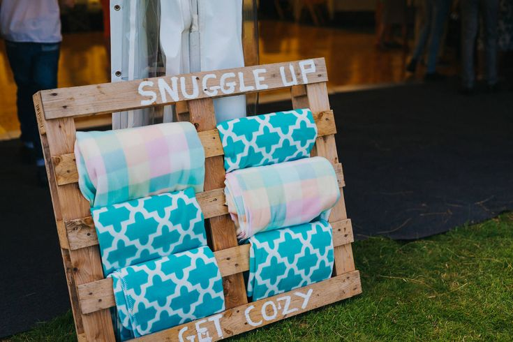 A must for any outdoor wedding. Just a crate, paint and rugs. Photo by Benjamin Stuart Photography #weddingphotography #rugs #cosy #outsidewedding #festivalwedding #snuggle #cratesign #attentiontodetail #forguests