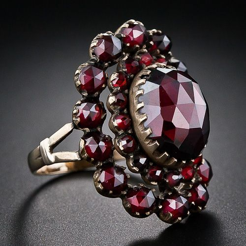 A sizable high-domed faceted garnet headlines this superb, all original antique Bohemian garnet ring. The center stone is surrounded by a double row of smaller garnets and the ring measures one-inch long. A nice one!