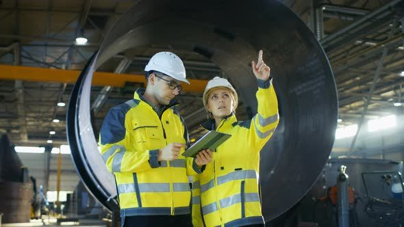 Male and Female Industrial Engineers Have Discussion while Using Tablet Computer.
