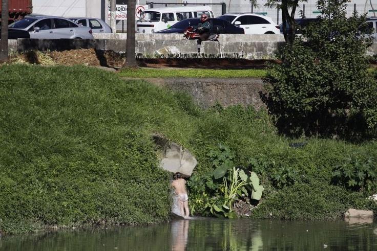 Homem toma banho em uma pequena queda d'água que sai de uma tubulação às margens do rio Pinheiros, na manhã de hoje, entre as pontes Eusébio Matoso e Cidade Jardim, zona oeste de São Paulo