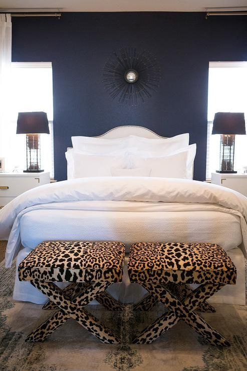 White and navy blue bedroom features an accent wall painted navy blue lined with a white curved nailhead headboard on bed dressed in soft white bedding flanked by white campaign nightstands placed below windows alongside a pair of leopard x benches placed at the foot of the bed.