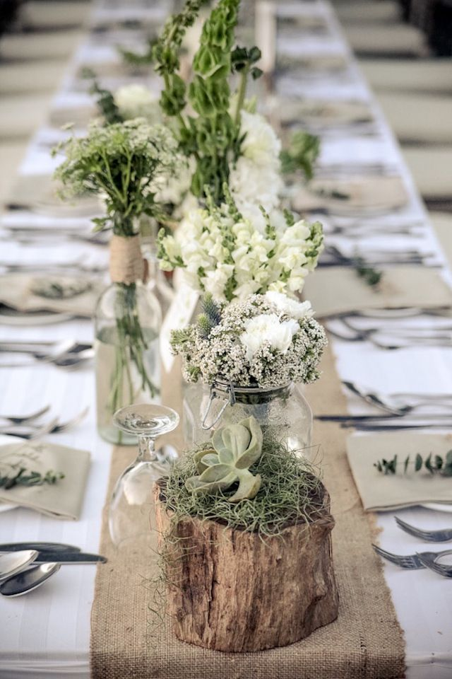 Long table arrangement with a board running down the middle with mixed glassware, greenery, and candles. Greens, tans, and white table linens.