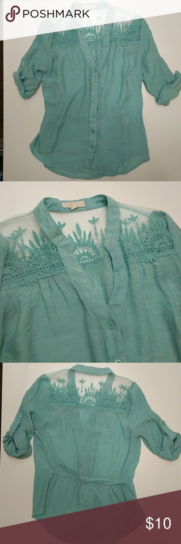Turquoise shirt Turquoise shirt with intricate detailing near the shoulders. The back has a tie that creates a flattering shape. In the first photo that white blob in the lower right hand side is the tag in the shirt, it is visible and can be removed. pearl Tops