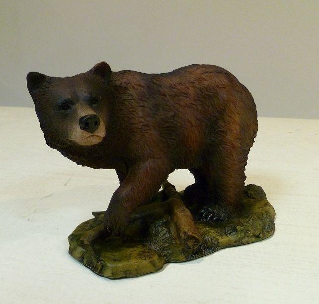 Een erg leuk klein dierenbeeld van een grizzly-beer op een plateau.