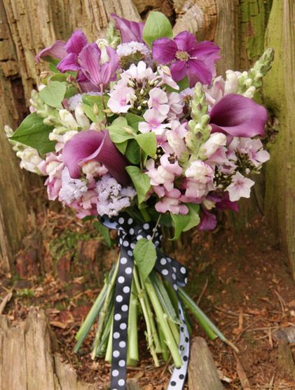 Informal hand-tied bridal bouquet of purple clematis, calla lily, snapdragon, phlox and static - the rich colours and loose shape would fit fantastically with a woodland wedding. Florissimo, Shropshire