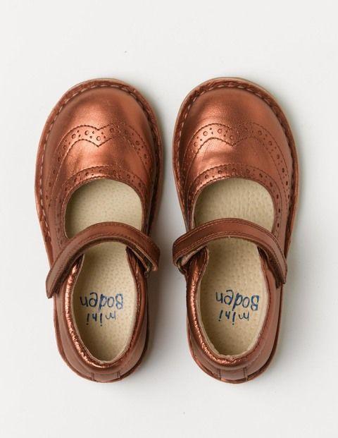 Wer einmal unsere Schuhe anzieht, will sie nie wieder hergeben. Diese glänzenden Spangenschuhe im Budapester-Stil haben einen Klettverschluss für einen sicheren Sitz beim Tanzen zu Hause oder beim Rennen zum Schulbus.