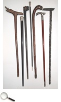 A set of seven walking sticks, three silver-handled, with the L-form stick comprising a sword in its shaft, the other four wooden handled ones depicting animal faces.