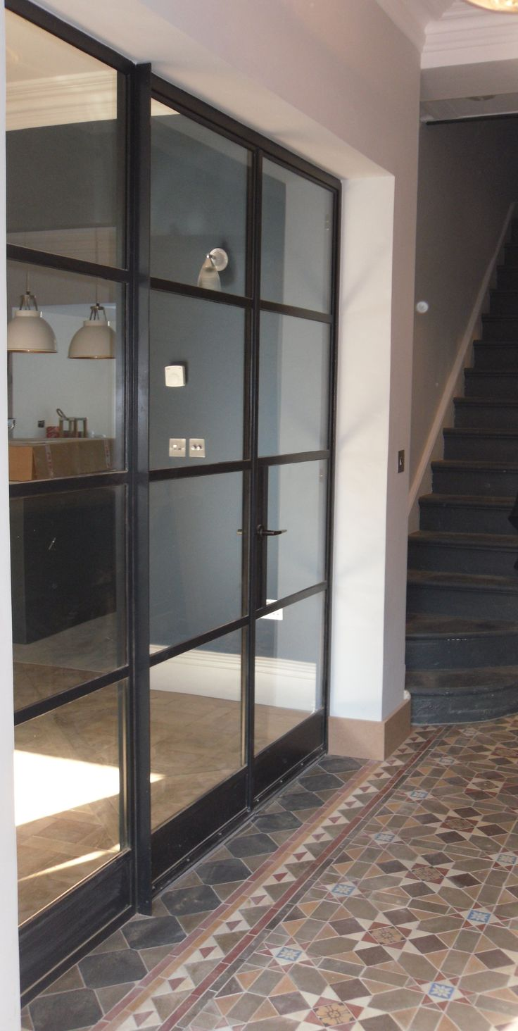 A Crittall door screen, by Lightfoot Windows (Kent) Ltd, handsomely separates this grand entrance hall and the other living spaces of this period property.