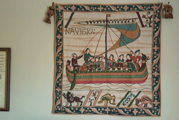"""Bayeux Tapestry Navigio wallhanging - a ship from Duke William of Normandy's armada sets sail on his invasion of Saxon England. This is a French tapestry woven today, seen in an office in Pennsylvania -  with the border 35""""x33"""" or also available with no border 29""""x27""""."""