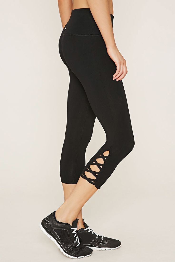 A pair of knit athletic leggings featuring crisscross cutout sides with a capri length and a hidden key pocket.