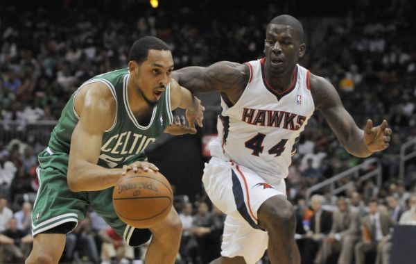 Boston Celtics center Ryan Hollins (L) drives past Atlanta Hawks forward Ivan Johnson in the second half of their NBA basketball game in Atlanta, Georgia April 20, 2012.