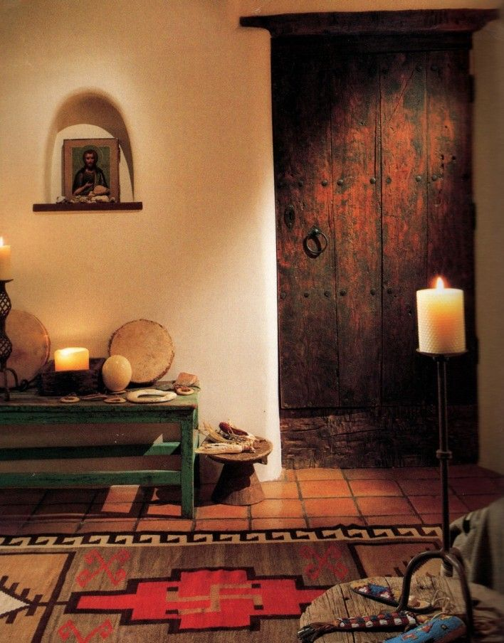 HACIENDA STYLE ARCHITECTURE AND DECOR - precious niche with the wooden ledge.. religious retablo.. rustic wood door with 'clavos'.. plaster walls.. tile floor.. bold design rug.. iron candle holder - Accents of Salado Furniture Store specializes in Hacienda Furniture and Accessories. See us on the web!