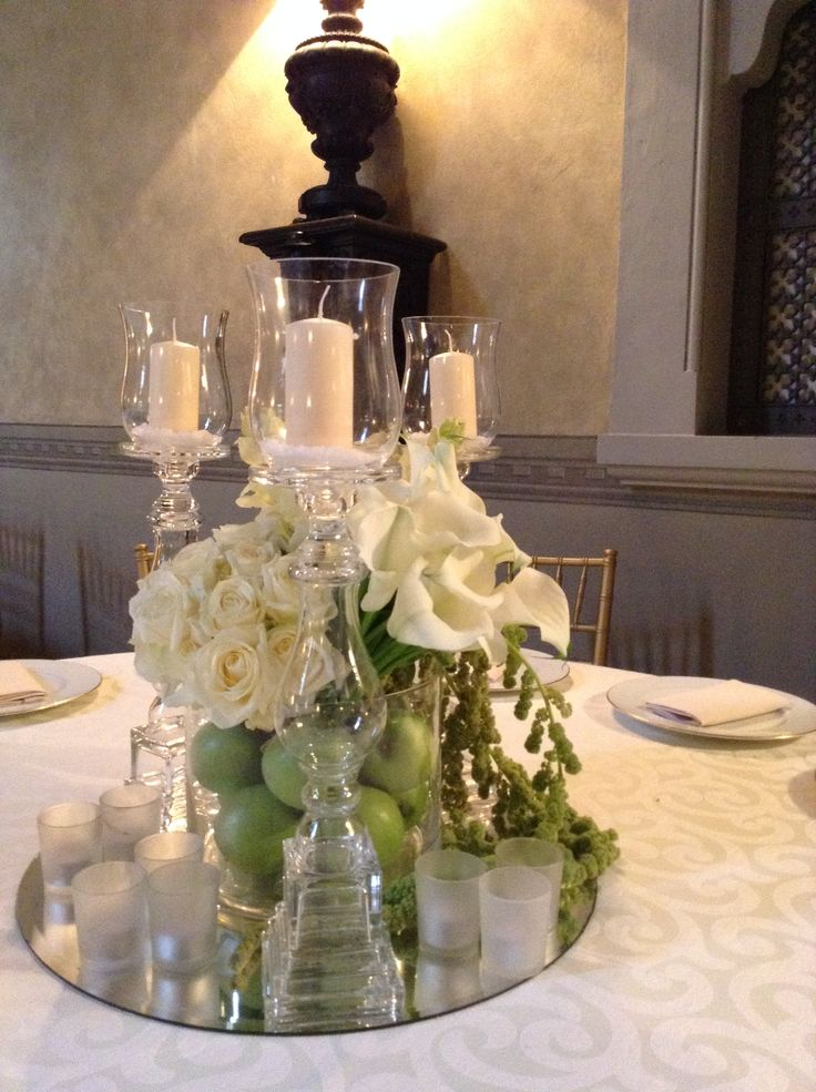 Flowers and fruits centerpiece with candles and mirror round top.