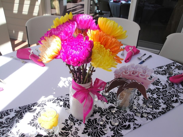 Table setup -- the centerpiece was a mason jar spray painted white with bright flowers from Costco wrapped with pink ribbon. Added a bowl of lemon drops for color and had the mustache and tiara game set up next to it. Finishing touch was the napkin rings!