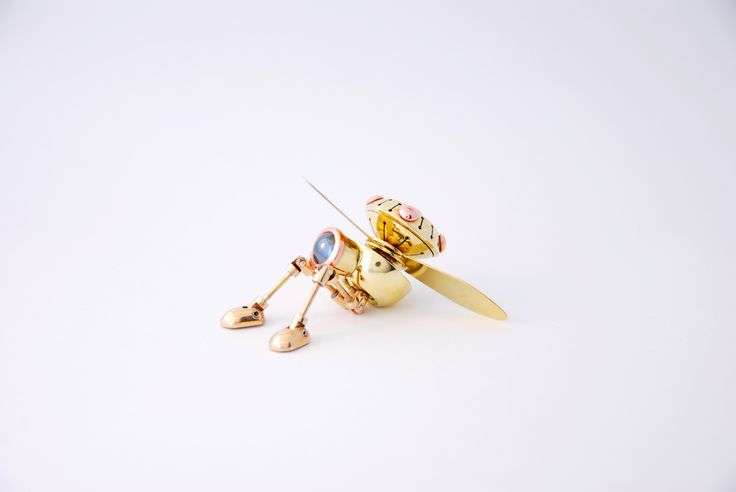 """Rotobot Mark 1 by Juhani Ananin. Steampunk miniature made from brass, bronze, copper and silver rivets with a cabochon cut hematite. 7 x 2,5 x 3 cm. Rotors 3,5 cm from the axle.  """"A good day for a bit of a flight.""""  Photo: Hanna Silander"""