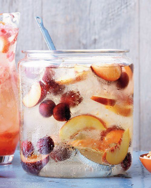 Stone Fruit Sangria - 1 peach, halved, pitted, and sliced into 1/2-inch wedges 1 nectarine, halved, pitted, and sliced into 1/2-inch wedges, 1 plum, halved, pitted, and sliced into 1/2-inch wedges 16 cherries, pitted, 3 tablespoons peach liqueur, 1 bottle (750 ml) dry white wine, such as Sauvignon Blanc, 4 cups (32 ounces) chilled ginger ale, Ice