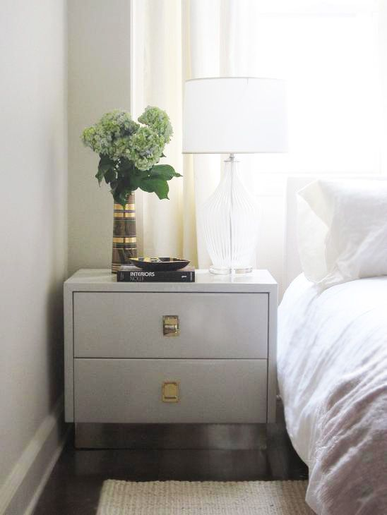 bedrooms - glass lamp glossy white lacquer 2 drawer nightstand white slipcover headboard jute rug Glamorous monochromatic bedroom with soft
