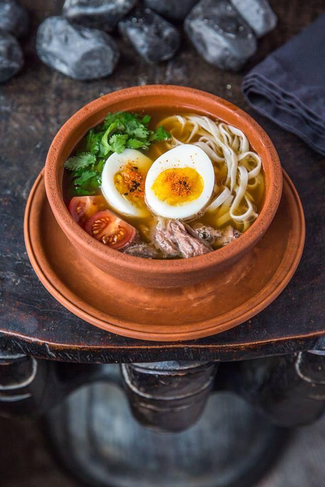 Рамен из бычьих хвостов и яичной лапши. Азиатский густой суп с лапшой, приготовленной в ручную, с кореньями и овощами, яйцом, черри, нежной мякотью от хвостов