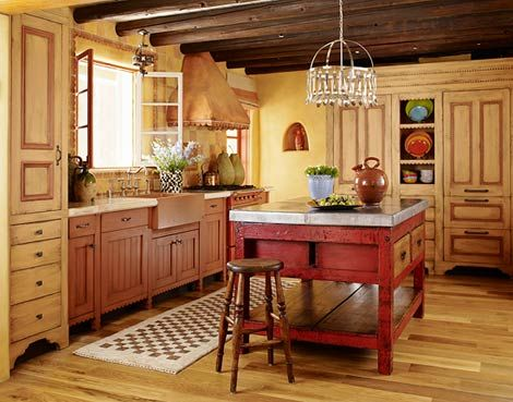 Scalloped trim, cabinetry feet, and multiple stain colors make it seem as though this Southwestern kitchen was assembled one piece of furniture at a time. Marching armoires house a refrigerator and a washer-dryer unit on opposite sides of the room. The island is an old store counter topped with zinc.