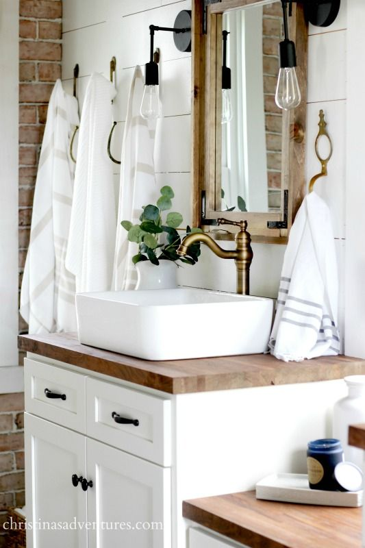 Vintage inspired farmhouse bathroom - lots of shiplap, white, wood tones, and mixed metals. You won't believe what it looked like before!
