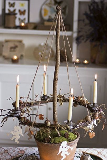 Candle wreath suspended over garden pot. Place several along the festive table for a rustic country look.