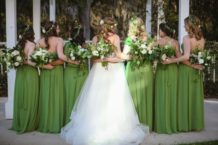 the bride and her bridesmaids hold their loose and unstructured bouquets of white roses, white larkspur, white ranunculus,white stock, white parrot tulips, white majolik spray rose, tuberose, white lisianthus,jasmine trails, bay leaf and magnolia leaf. the bridesmaids in green gowns wear flower crowns of white ranunculus, roses, chamomile and greenery.