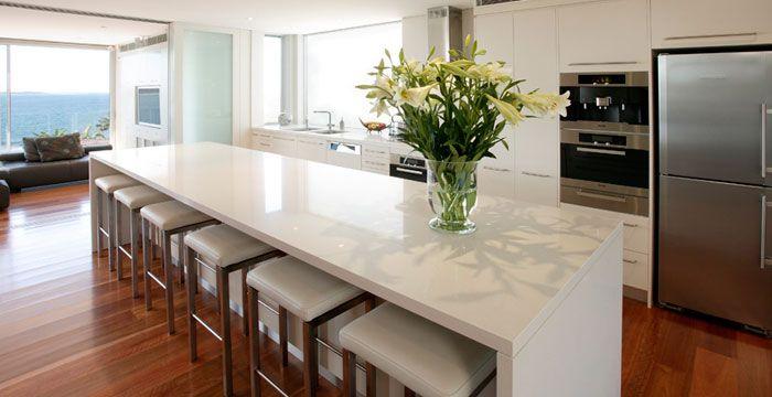 Eggshell Caesarstone Quartz counter, white Ikea cabinets and wood floors. +colorful backsplash.