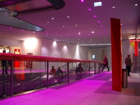 Villach, Austria. The saturated color gives the space a warmer feel because pink is a warm tone. At the same time, this color can distort people's view of the store because the whole place is saturated in this pinky-purple color. The red elements still stand out in the store.