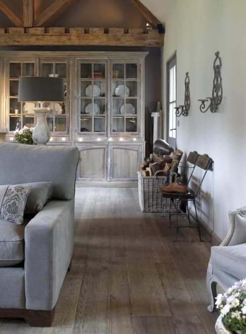 Antique gray hardwood floors set the stage in a French-influenced rustic living room.