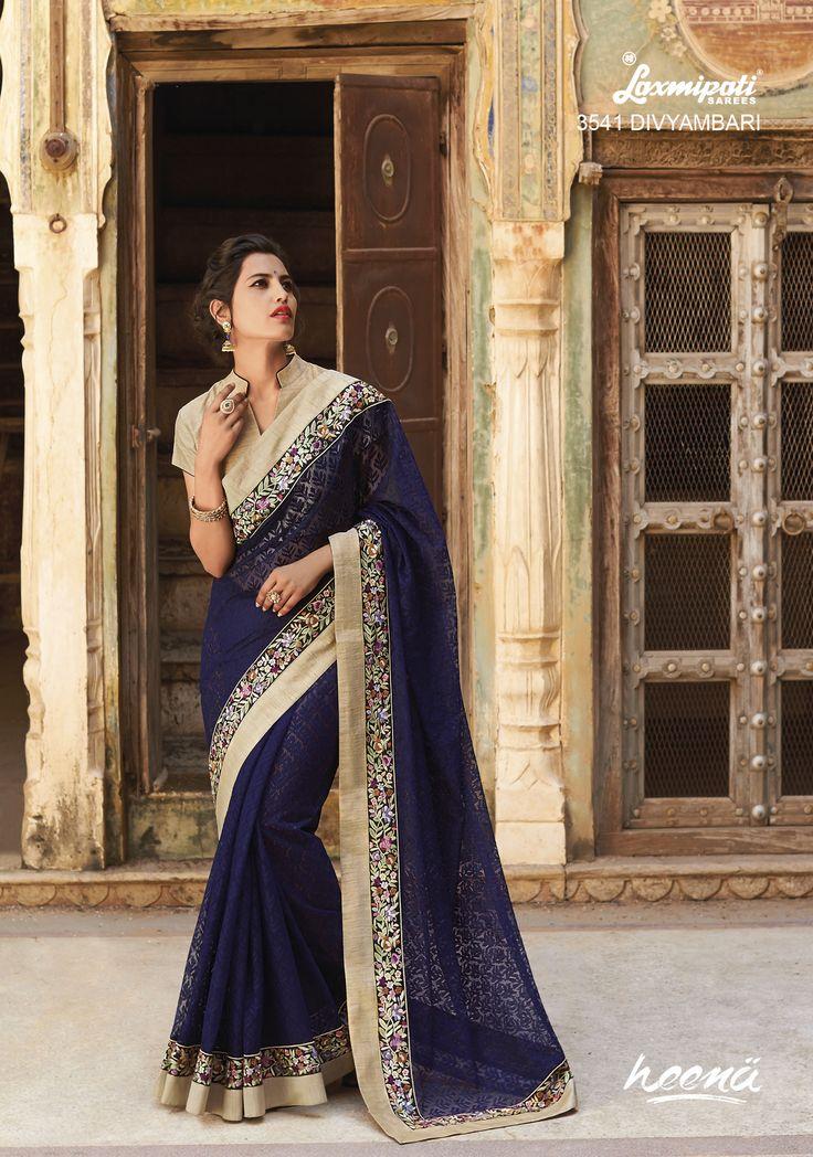 Alluring navy blue jacquard saree with heavy resham work border and rawsilk blouse.