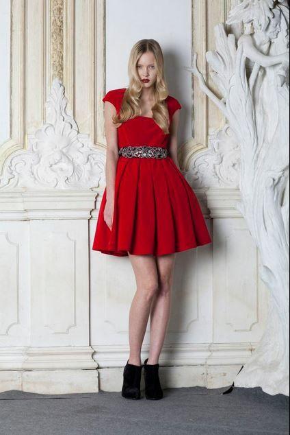 Backstage at the LUBLU Kira Plastinina Fall 2013 Fashion Show. Model in red Plush cap sleeve dress and rhinestone wrap belt.