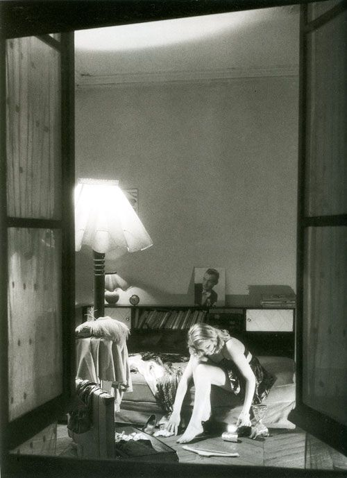 A young girl sitting on her bed, seen through her open window, Willy Ronis, 1946
