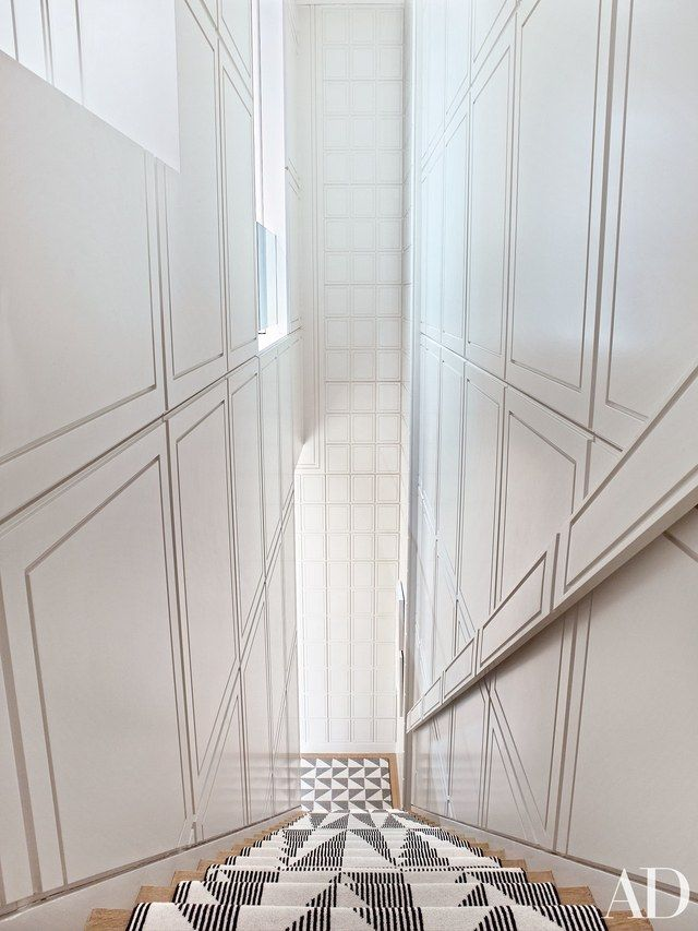 The dramatic staircase is lined with panels painted a Benjamin Moore white | archdigest.com