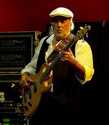 John Graham McVie (born 26 November 1945) is a British bass guitarist best known as a member of rock groups John Mayall & the Bluesbreakers and Fleetwood Mac. His surname, combined with that of Mick Fleetwood, was the inspiration for the band's name. He joined Fleetwood Mac shortly after its formation by guitarist Peter Green in 1967, replacing temporary bassist Bob Brunning