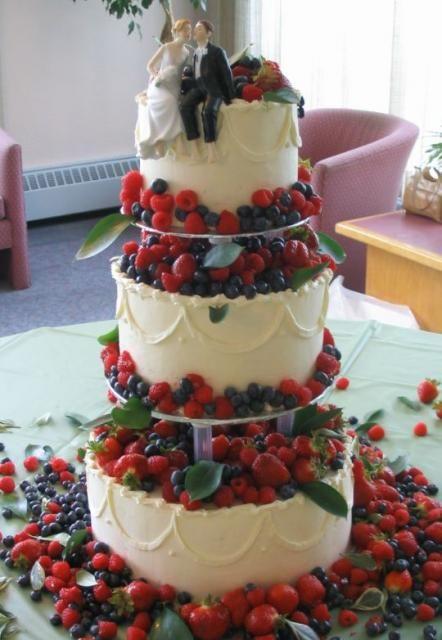 Wedding cake with rasberries strawberries and blueberries in 3 tiers. Maybe? Just strawberries. Strawberry shortcake. Yum.