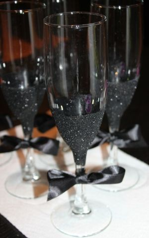 DIY Black Glitter Champagne Flutes. Use glass glue, paint brush, black glitter, and a steady hand. Of course you can use any color glitter, but black is sexy.