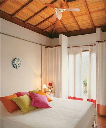 O quarto dispõe de prateleiras de madeira e alvenaria vedadas com leves cortinas de algodão.