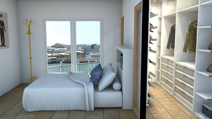 Vestidor tras pared de cabezal de cama, con entrada por puertas laterales.