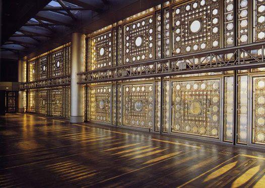 """A fachada do Instituto do """"Institut du Monde Arabe"""", em Paris, com design de Jean Nouvel, tem uma releitura do muxarabi. Nessa releitura, a madeira foi substituida por diafragmas que controlam a entrada de luz no interior do edificio. O conjunto dela lembra também um grande tapete persa."""