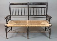 """In the manner of William Morris, an ebonised """"Sussex"""" style  double chair back settee with turned spindles, scroll arms and rush seats, raised on ring turned tapered legs, late 19th Century 47""""w SOLD £360"""
