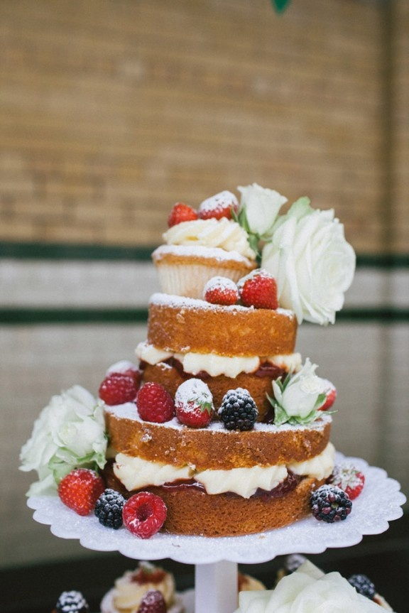 a small naked wedding cake filled with cream, jam, and covered in flowers and berries.