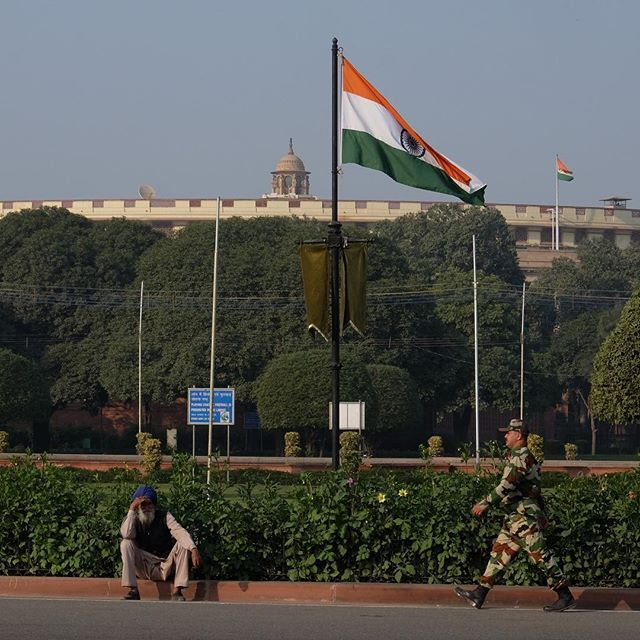 A symbol of #India - the #parliament building in #Delhi with the #Indian #flag 🇮🇳flying high caught our attention as it stood in the middle of this Sikh #citizen and one of the many brave #Indianarmy jawans #patriotic #capital #photooftheday #instahappy #fuji #nofilter #streetphoto #streetphotography #marching #saffron #orange #green #traveling #trip #persona #people #connection #delhigram @indiatravelgram @photographers.of.india #peopleofindia #soldier #bluesky