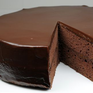 Flourless Chocolate Cake with Chocolate Glaze - Gluten Free | This moist and dense chocolate cake is topped with a smooth, rich dark chocolate ganache that melts in your mouth. Serve it with sweetened whipped cream and raspberries for a delightful and elegant desert.