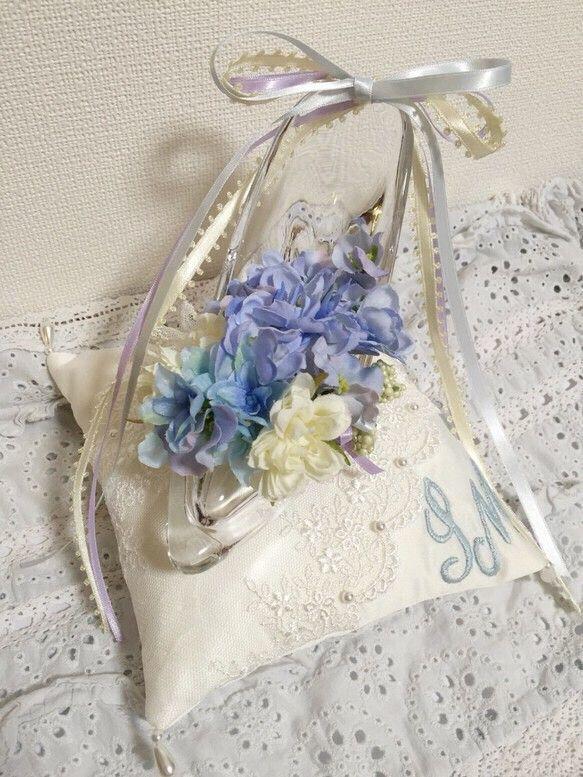 新郎新婦様のイニシャルを入れられる、セミオーダーのリングピローです♡シンデレラのガラスの靴をイメージしました。コサージュのついたガラスの靴をイメージし、優しい色合いのお花と、上品なライトシルバーのチュールレースで飾り付けました。見本画像のように、ライトグリーンのつぶつぶのお花にリングを引っ掛けられる様にしています。サイズ クッション H15.5×W15.5㎝ ガラスの靴のみ H10.5×W6.0×D13.0㎝*****************************************************************************************************クッションの右端にお好きなイニシャルの手刺繍を入れることができます。ご新郎様、ご新婦様それぞれのイニシャルをご連絡ください。画像は 新郎様 H 新婦様 Y…