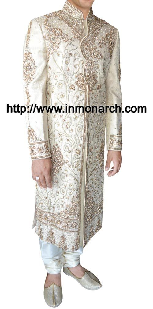 Traditional groom wedding sherwani made from cream color brocade fabric. Hand embroidered as shown. It has bottom as chudidar made from dupion fabric in white color.