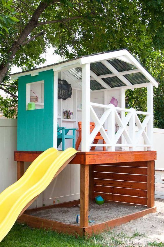Learn how to build a wooden outdoor playhouse for the kids. This DIY playhouse has it all: sandbox, climbing wall, slide and clubhouse! Housefulofhandmade.com #buildplayhouses #gardenplayhouse