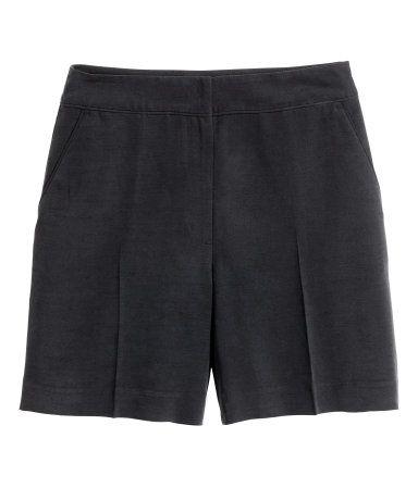 Svart. Ett par shorts i mjuk, vävd kvalitet med pressveck. Shortsen har sidfickor och fuskfickor bak. Hög midja. Knäpps med hyska och hake.