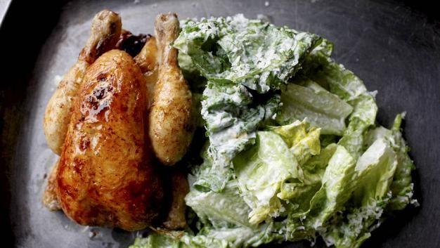 Kokonaisena paistettu kana tarjoillaan caesarsalaatin kanssa.