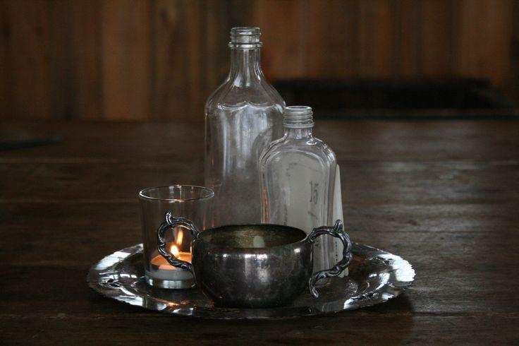 Antique charm. Vintage silver platter and sugar dish. Vintage bottles. Votive candle and holder.   Needs flowers in the vintage bottles, sugar dish, and perhaps a bud on the opposite side.  https://www.facebook.com/focalpointdesignsanddecor